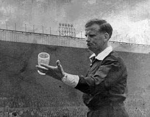 Referee David Smith, known professionally as DW Smith, holds up a glass which was thrown at him during a match between Leeds and Liverpool at Elland Road, Leeds, on May 4, 1968