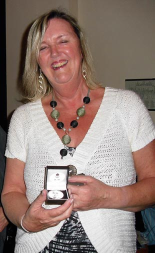 Lyn Cook receives her silver medal to commemorate 25 years with the English National Opera