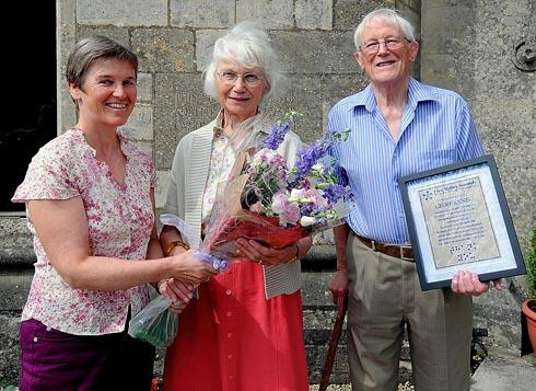 Five Valley Sounds committee member Judy Gowans (left) presenting a bouquet to Maggie Annis (centre) with her husband Geoff Annis, who holds a certificate presented to him by the charity