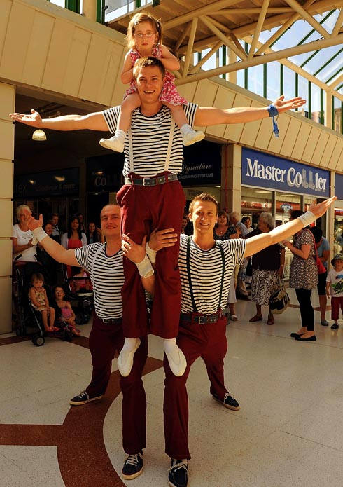 Acrobats from Giffords Circus performing in Merrywalks Shopping Centre with volunteer Gracie Macintosh, three