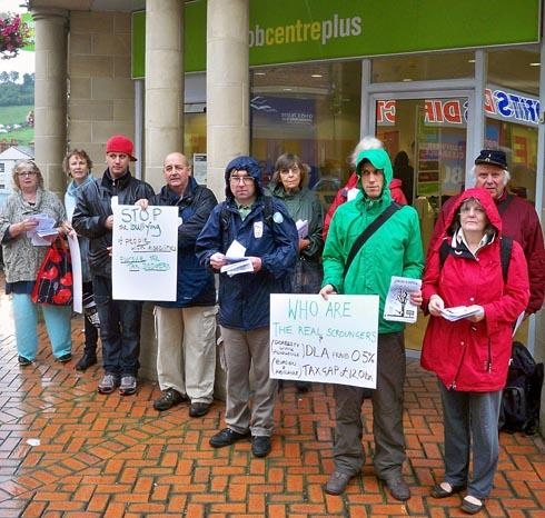 Protestors from action group Stroud Against the Cuts demonstrating outside Job Centre Plus in Stroud to oppose Atos Healthcare's sponsorship of the London 2012 Paralympic Games. Campaigners accuse the firm of unfairly cutting disability benefits