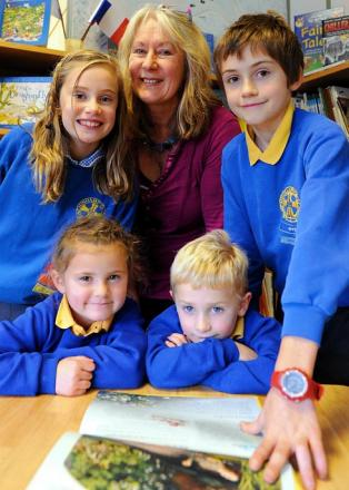 Minchinhampton Primary School teaching assistant Sally Savage with pupils in the school library. Mrs Savage is leaving after 23 years