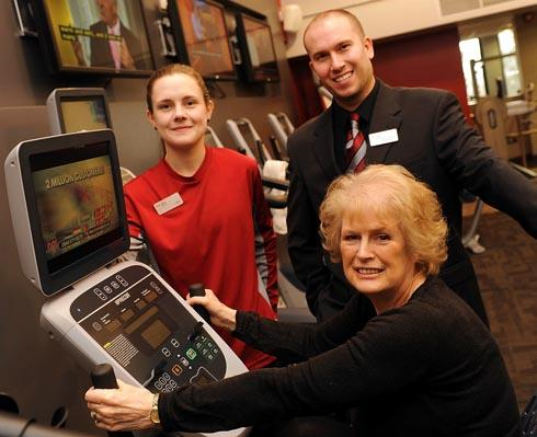 June Cordwell, executive member for community services at Stroud District Council trying out one of the machines at Stratford Park Leisure Centre gym, with Jade Adlam, fitness motivator, and Dan Coleman, general manager