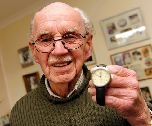 Graham Furley holding the watch presented to him.
