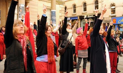 Participants in the One Billion Rising flash mob outside the Sub Rooms holding their index fingers aloft to show support for women and girls around the world