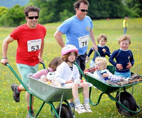 Baker Brother Tom Herbert (left) and pal Tom Howard took part in last year's Race4All on Minchinhampton Common with their children in wheelbarrows