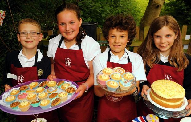 (l-r) Samuel Hendrie, 10, Freya Gardiner, 11, Alexander Owusu, 10, and Hannah Dawkins, 11, selling cakes at the Rosary Primary School garden party on Friday, June 7