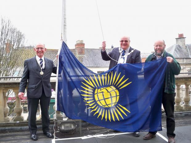 (l-r) Stroud Town councillor Haydn Sutton, Stroud District Council chairman Dennis Andrewartha and Cllr Simon Pickering, chairman of SDC's environment committee, raising the Commonwealth flag at the Subscription Rooms this morning to mark Commonweal