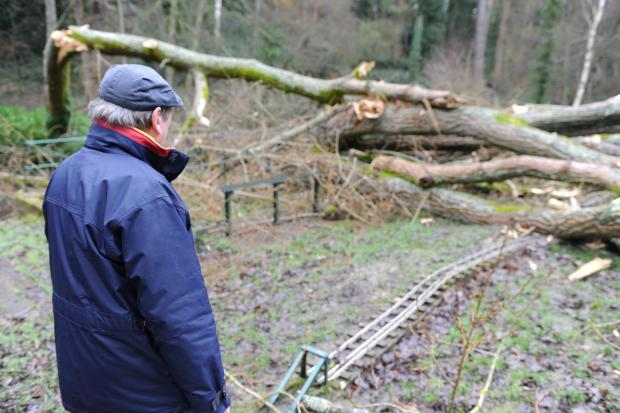 Jim Stone, a member of the model railway club, inspects the damaged caused to the track by a large fallen tree in Stratford Park