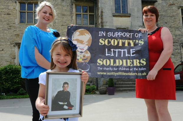 Rosie Lamb holds a picture of her Dad who was killed in Afghanistan, pictured with mum Melissa (left) and Sara Clark who are holding a charity ball to raise money for Scotty's Little Soldiers