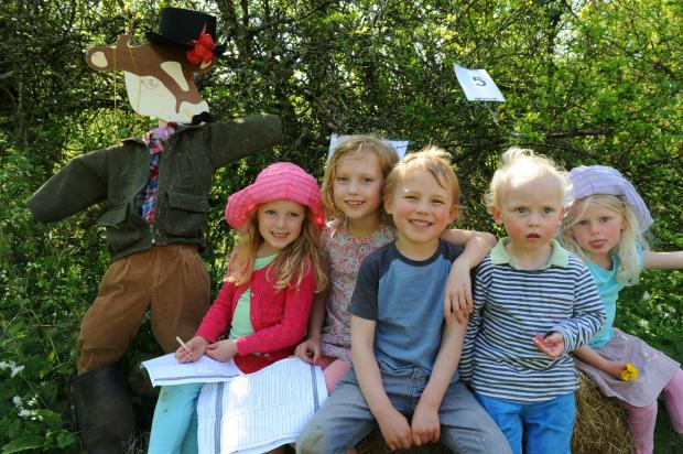 (l-r) Scarlett Johnson, five, Madeline Peters, seven, Freddie Peters, four, Eden Peters, two and Darcy Johnson, three with Dandy Dexter cow on the Amberley Cow Hunt