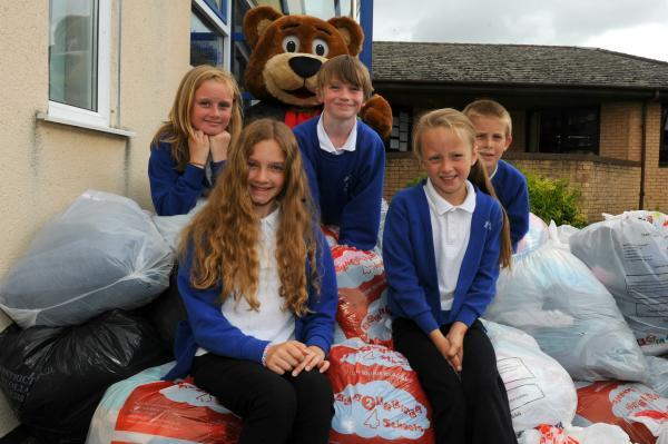 (l-r) Kiera Neve, 10, Amy Smalley, 11, Simon Bermingham, 10, Alisha Lonsdale and Alfie Ball, eight, on top of the textiles that Park Junior School have collected for Rags2Riches