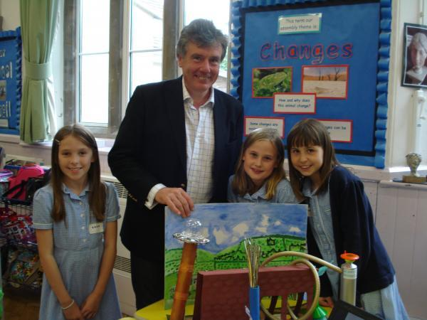 Photograph of Neil Carmichael MP with Lucy, Poppy and Isa from Class 4 Eagles, and their model of the future of Caple's Mill.