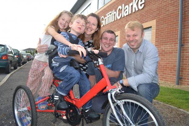 Toby Dinwoodie, aged 4, with his sister Daisy Dinwoodie, 7, mother Jenny Seeley, father Ryan Dinwoodie and (far-right) Julian Owens, of the Stonehouse based chartered accountancy firm GriffithClarke, which has bought Toby the specially-designed new trike