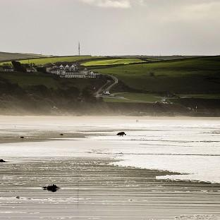 The pair were taken from the water at Woolacombe Beach in north Devon amid 'heavy' surf conditions in the region