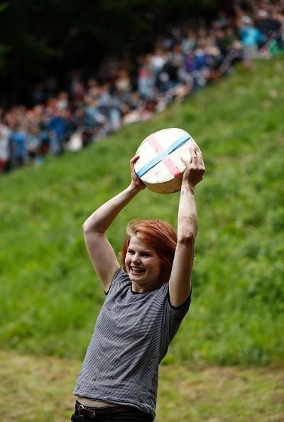 Florence Early, 25, from Sheepscombe holds her cheese aloft after winning the women's race in the annual Cooper's Hill cheese rolling competition near Cranham on Bank Holiday Monday. Pictures by Adrian Dennis/AFP/Getty Images