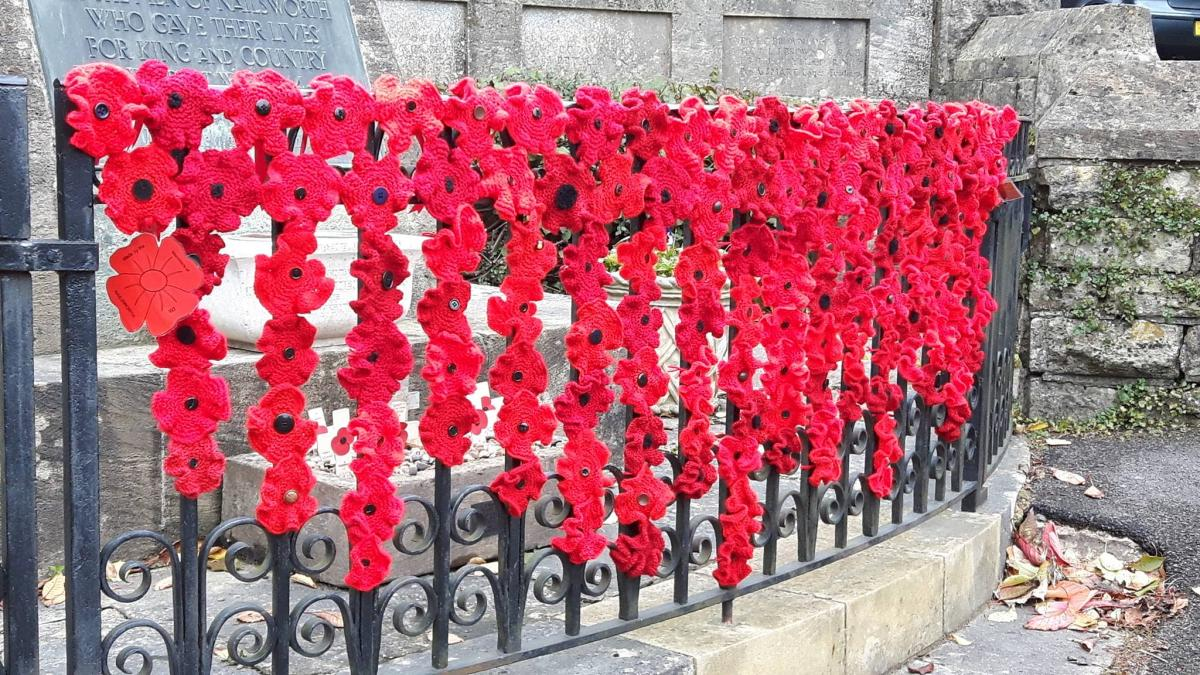 nailsworth wi yarnbomb war memorial with knitted poppies ahead of