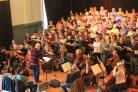 The Refugee Aid Choir and Orchestra being rehearsed by Hugh Barton, with co-conductor Philippa Morgan sitting behind
