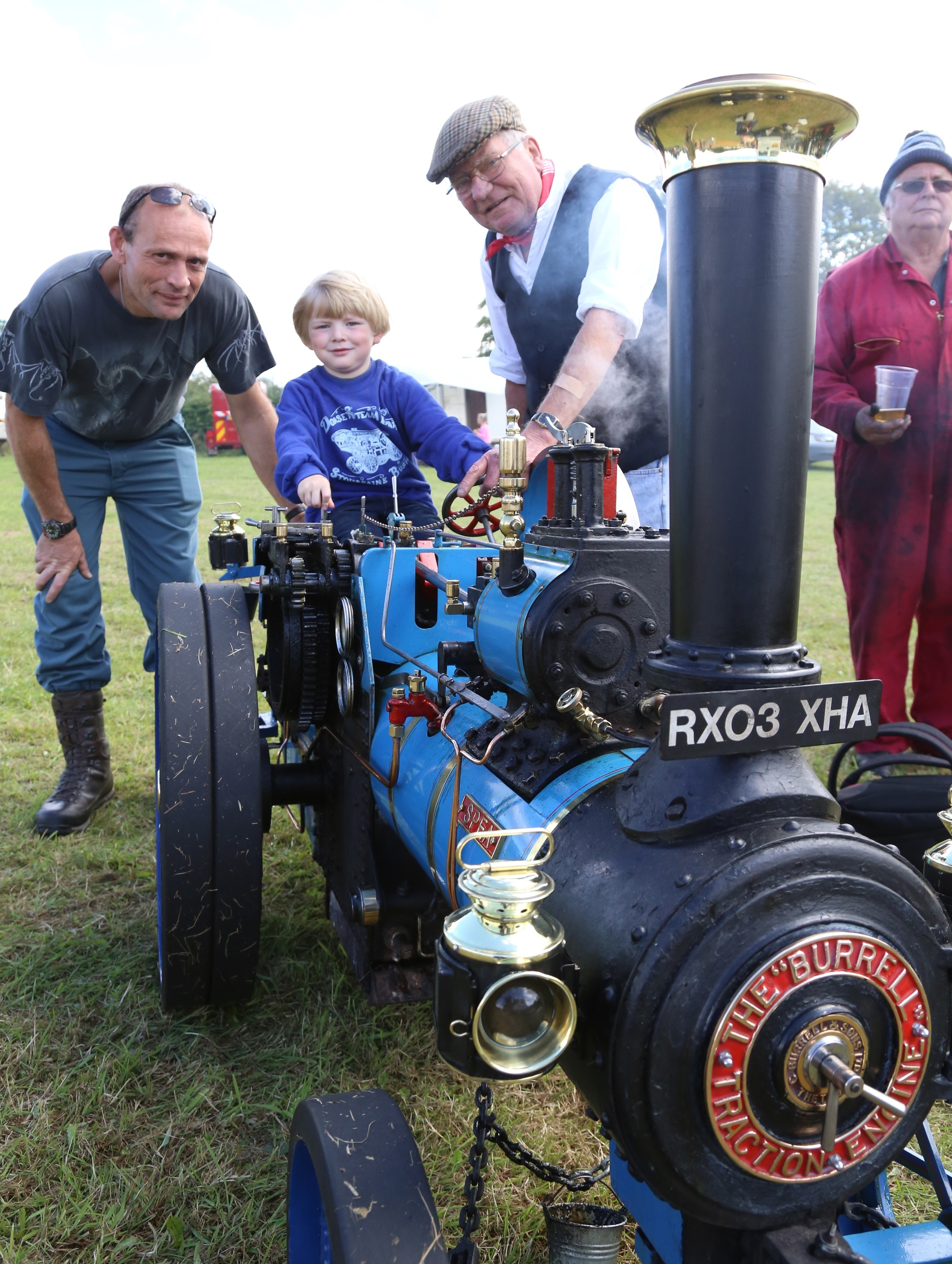 Michael Dixey and son Tommy from Fossebridge are shown a 4 1/2 inch scale agricuktural engine by owner Bob Gaskell at Northleach Steam Show.