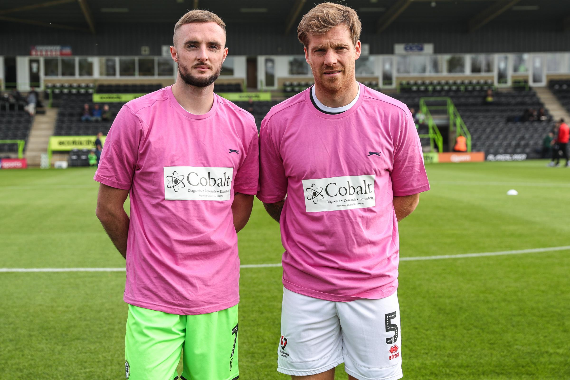 Forest Green Rovers Carl Winchester(7) and Cheltenham Town's Jonny Mullins sport the pink t-shirts supporting charity Colbalt during the EFL Sky Bet League 2 match between Forest Green Rovers and Cheltenham Town at the New Lawn, Forest Green, United